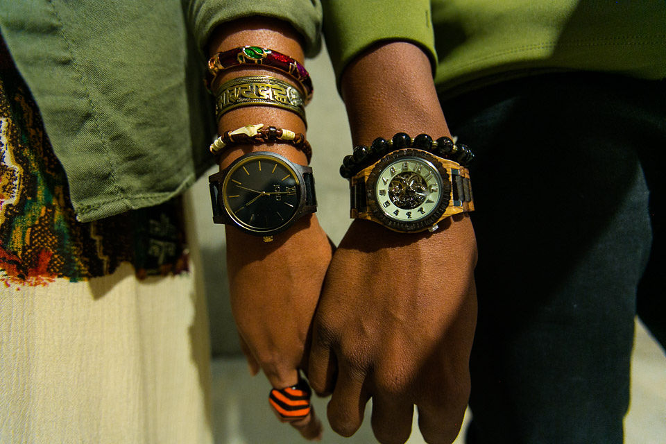 black couple holding hands wearing wood watches