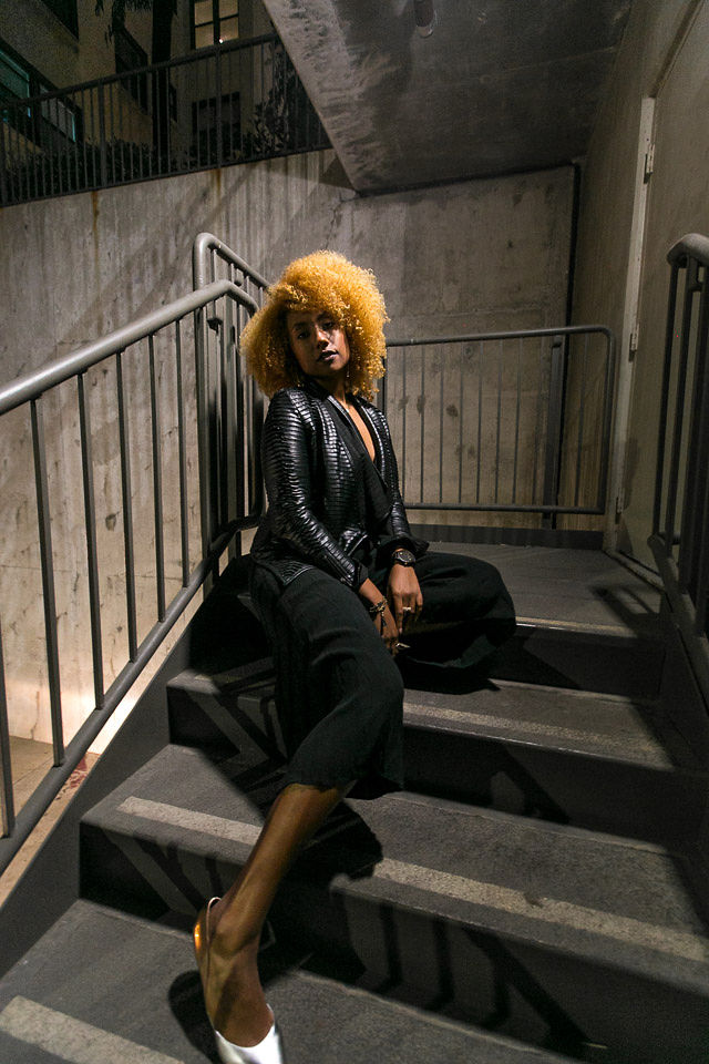 woman sitting on stairs wearing all black outfit and silver shoes