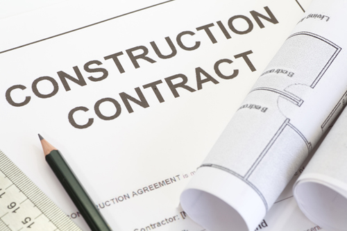 A construction contract with rolled up paper, a pencil, and a ruler