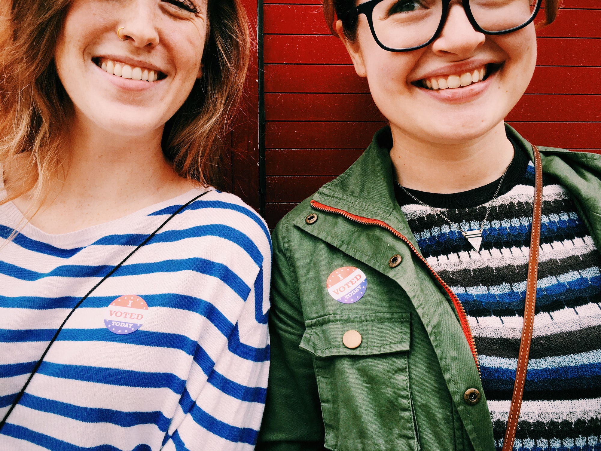 """Two young woman wearing """"I VOTED"""" stickers."""