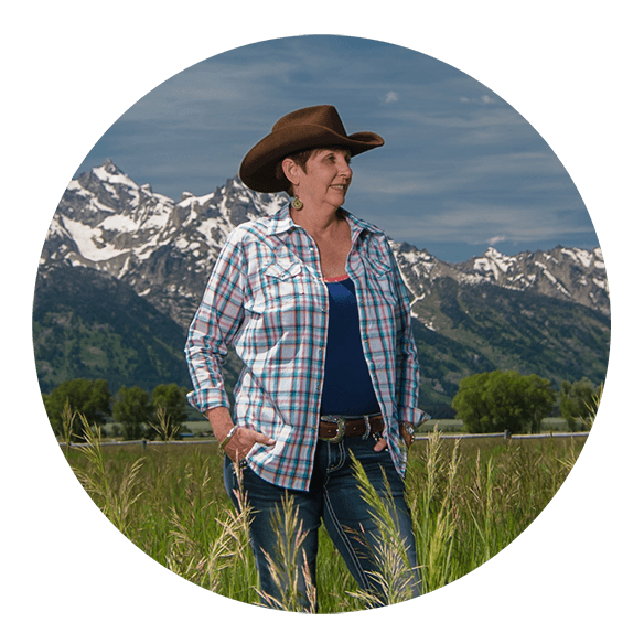 Dr. Laura Bush in cowgirl hat with Grand Tetons in the background