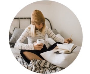 Woman sitting in bed with coffee reviewing her writing in a notebook