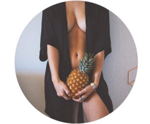 Woman in robe holding pineapple