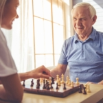 Man playing chess with caregiver.