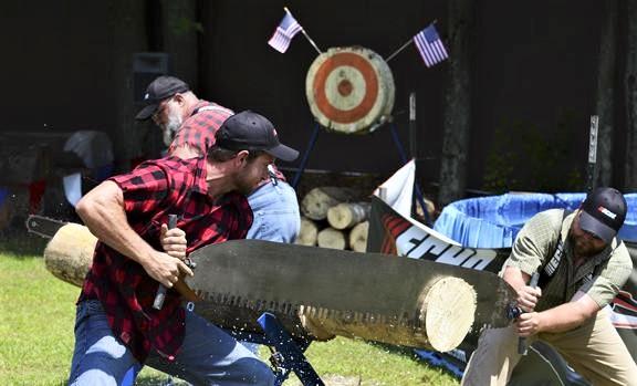 At the Saratoga County Fairgrounds, The Paul Bunyan Lumberjack Show performed for a audience. Lyle LeCaptain, left, and Robert Kane competed against Lee LeCaptain with a hand saw and a chain saw.Photo Erica Miller 7/16/13 news_Lumberjack1_Wed