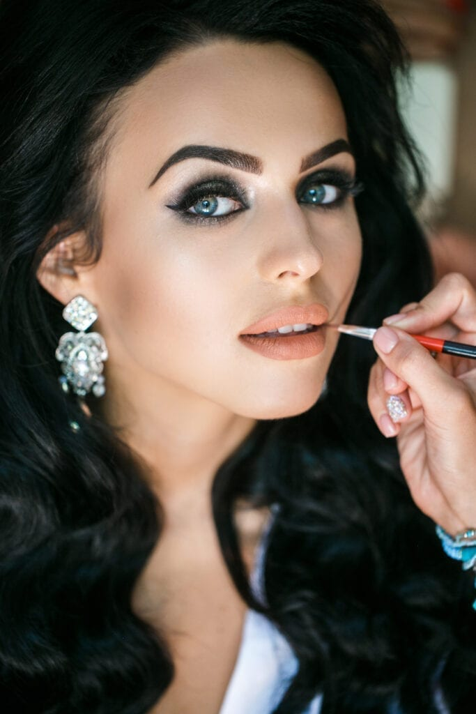 beautiful bride getting her makeup touched up
