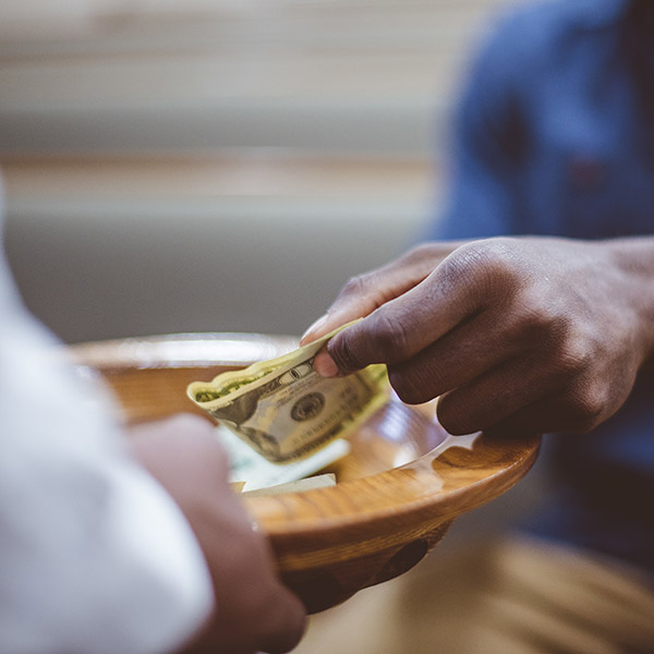 A closeup shot of a male donating money for church with a blurred background