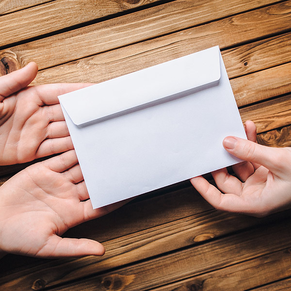 Hand pass the white envelope to the other hands on a wooden background. Transfer of money for donation. To send a letter.