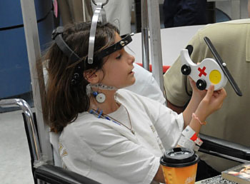 Image of girl in hospital with wooden toy helicoper
