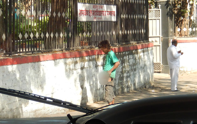 An Indian man relieving himself on the sidewalk outside our bus.