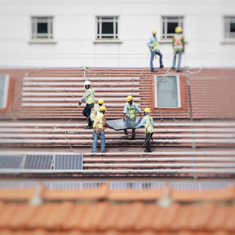 Men installing photo panels on a roof.