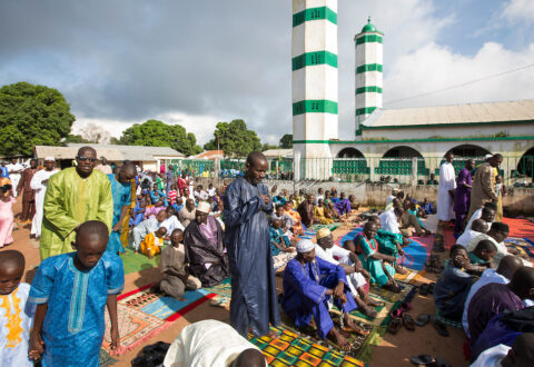 Gambian Muslims, both young and old, fill the local mosque in Sinchu and every available space outside to pray during the first day of Tabaski. Eid al-Adha, or known as Tabaski in West Africa, is also called the Feast of Sacrifice. Celebrated throughout the Muslim world is the second of the two Eid celebrations. During Tabaski every family will buy a goat which will be sacrificed and the meat distributed between the family and friends.