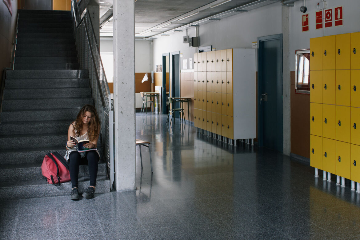 Student Reading In An Empty Corridor