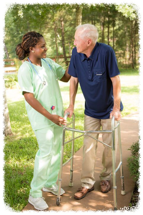 elderly man walking with assistant