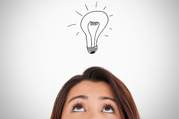 Brunette woman looking up with an illustrated light bulb