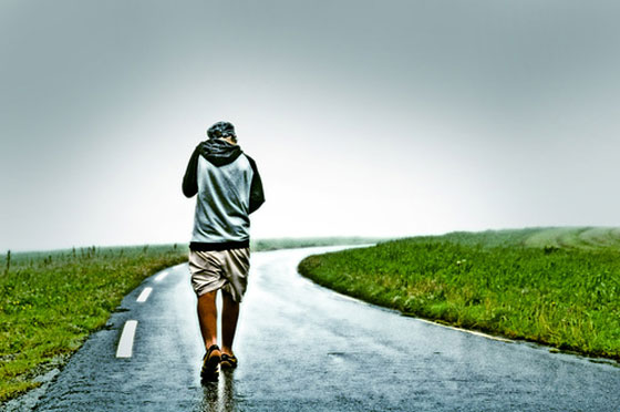 man-walking-away-on-lonely-road