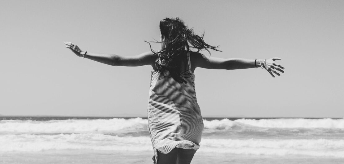 Woman with open arms facing the beach change your beliefs and change your life Leben ändern
