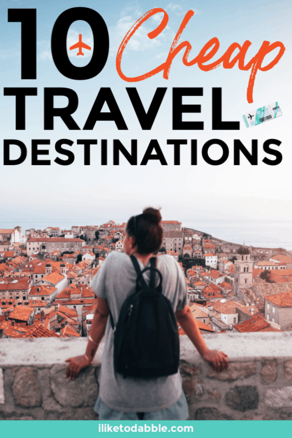 Cheap travel destinations to visit this year. Cheap international destinations to travel to. Saving money on travel. Budget travel tips. Budget traveler. Image of woman looking out into a city. #cheaptravel #budgettravel