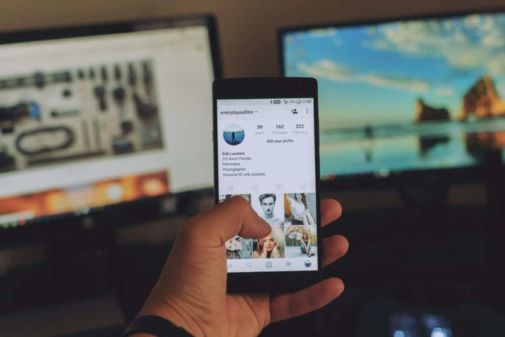 online jobs for college students in post image 1. Image of looking at Instagram through mobile phone.