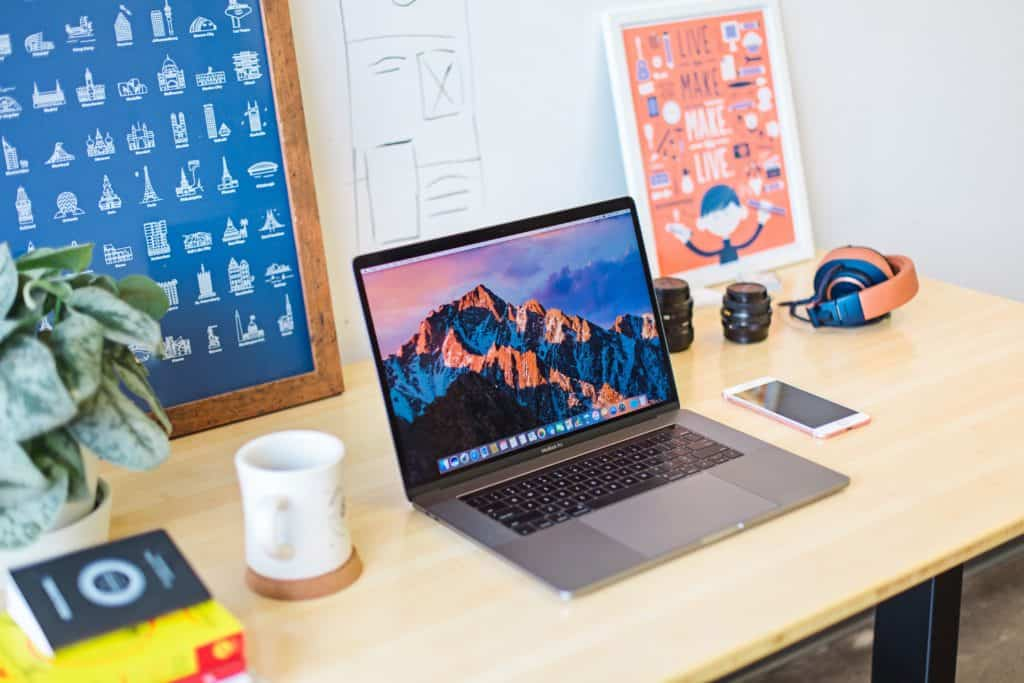 online jobs for college students in post image 4. Image of laptop, coffee mug, pant, and headphones on desk.