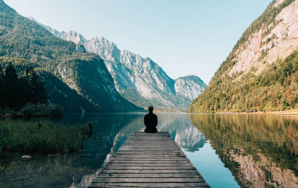 ways to make your credit card work for you in post. Image of person sitting on a dock looking our at a river surrounded by mountains.