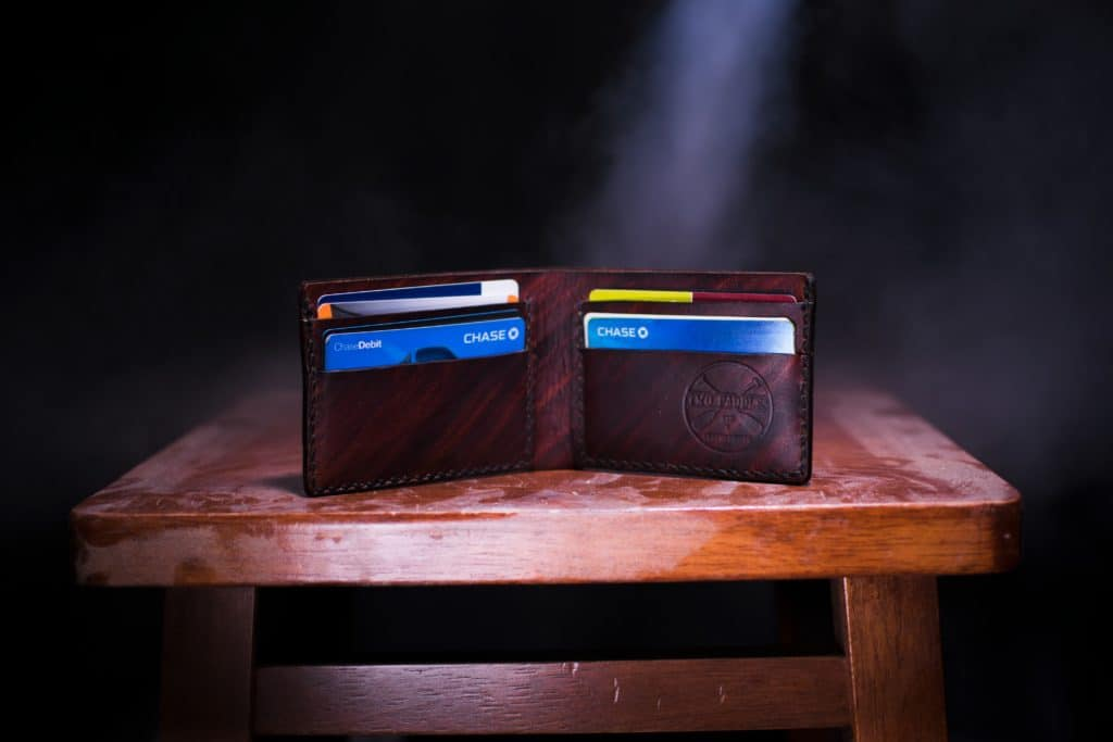 Ways to make your credit card work for you in post. image of opened wallet with credit cards on table.