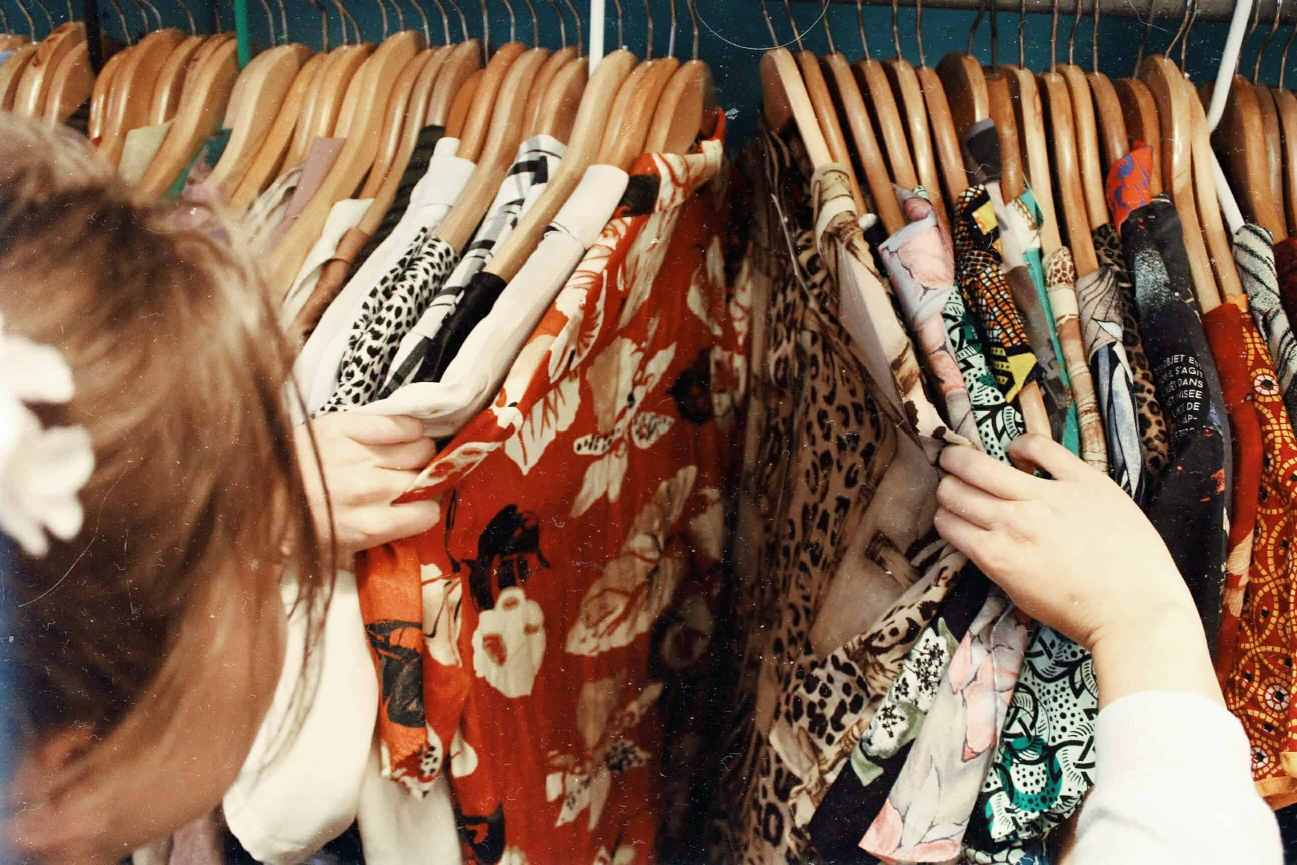 thrift store flipping clothes. Image of women going through her clothes within her closet.
