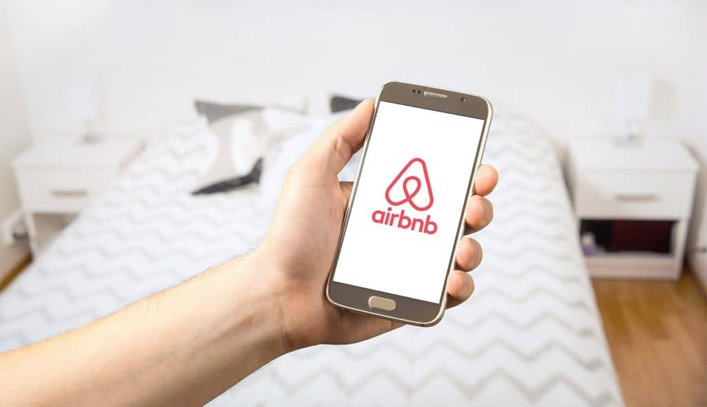 How to become an airbnb host content. image of person having their phone on the Airbnb app.