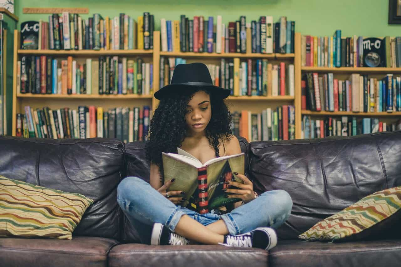 Hobbies that make money - reading - woman sitting on couch reading a book surrounded with a bookshelf in the background.