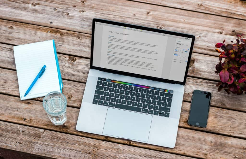 image of laptop, journal, pen, cellphone and flowers on a wooden table.