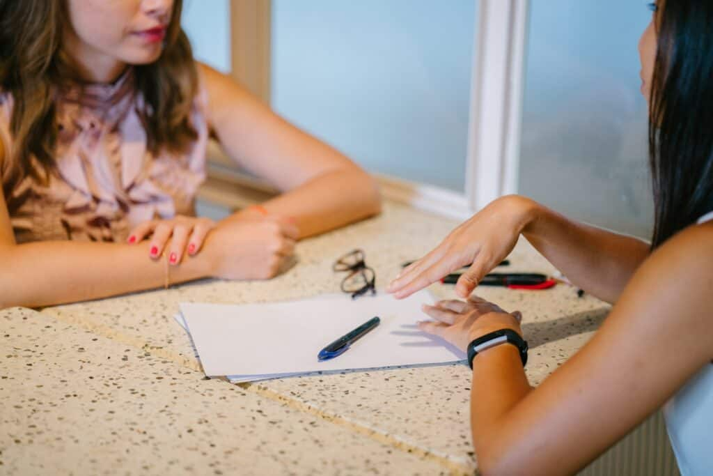 Image of woman consulting another on her business. Both are looking at a business plan on the table.