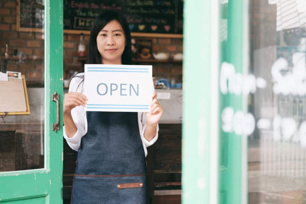 """support small business in post image of coffee shop and worker in smock holding """"open"""" sign."""