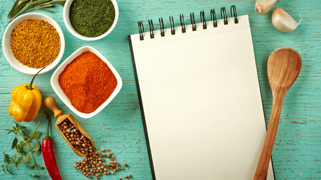 Spices, vegetables, notebook, and wooden spoon on a table
