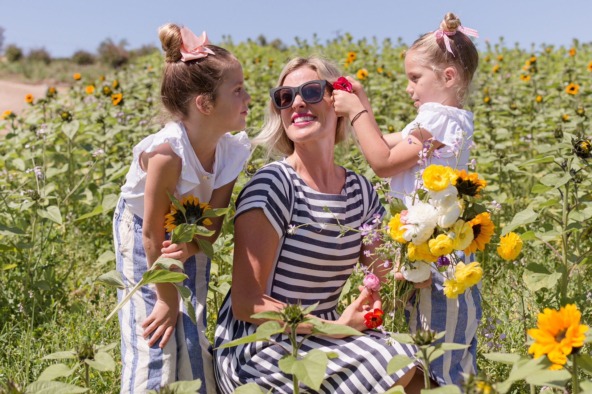 Blonde San Diego Mom in field of sunflowers wearing a striped dress wearing sunglasses smiling with her two young daughters