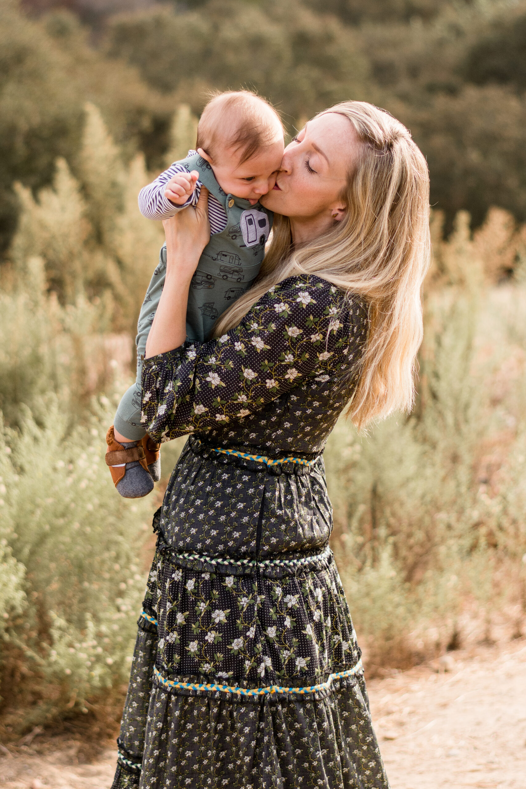 Mom in a green dress holding her infant son kissing his cheek during San Diego family photo shoot