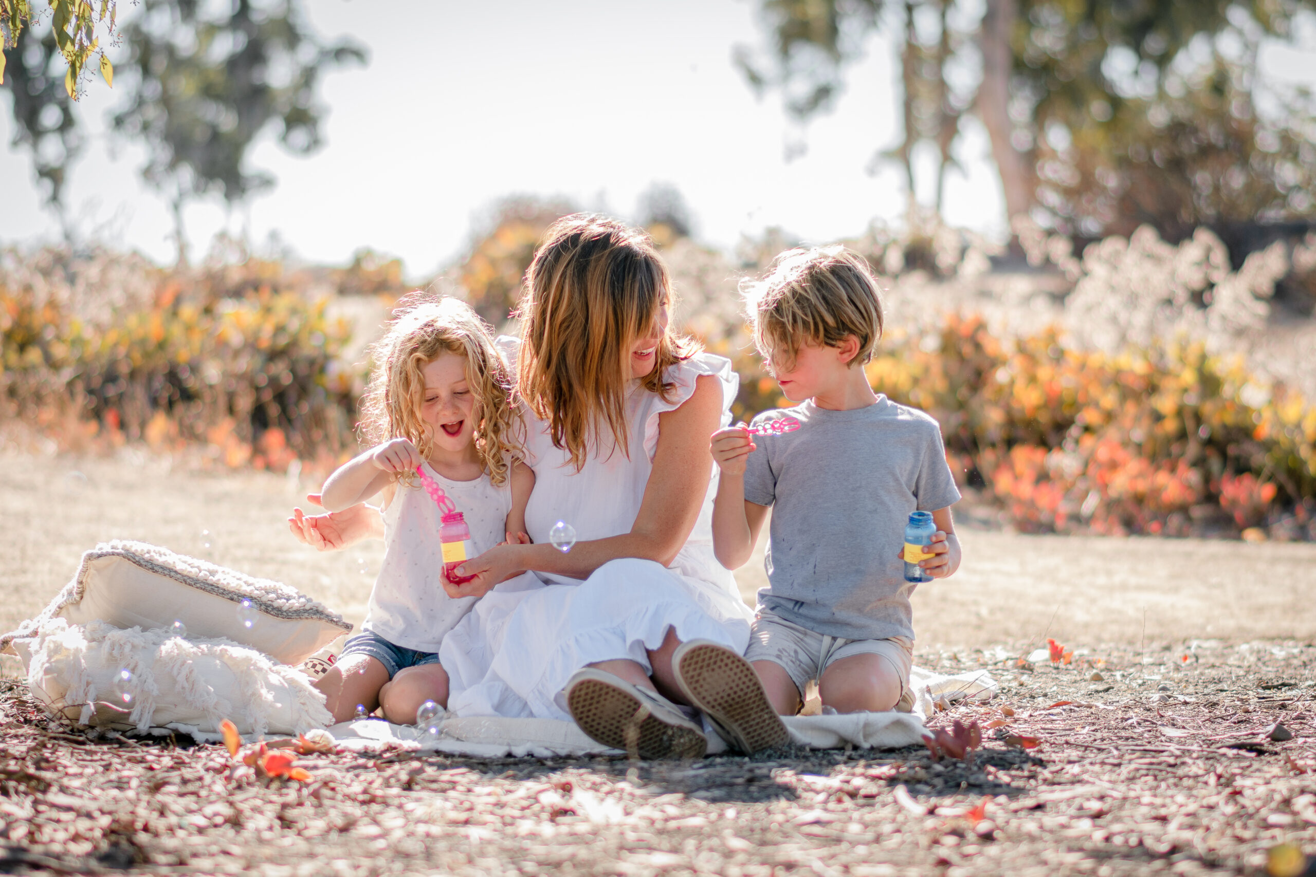 Lifestyle Photo of a Mom and two children sitting on a blanket and blowing bubble in a San Diego Park