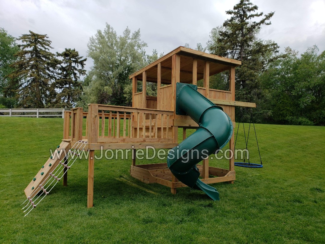 8'x8' Clubhouse with slanted wooden roof, 6' Deck height, 8'x8' Uncovered porch, 4' Deck height, (8'x16' Footprint), 7' Enclosed spiral slide, 3' Cargo net & Rock wall entry, 3' Cantilever with Web swing & 4'x8' Framed sandbox