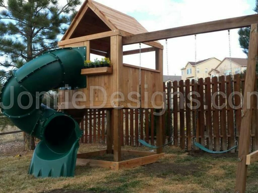 5'x5' Clubhouse with wooden roof, 4' Deck height, 5' Enclosed spiral slide, Rock wall entry, 8' Swing beam with 2 Standard swings & Flower planter