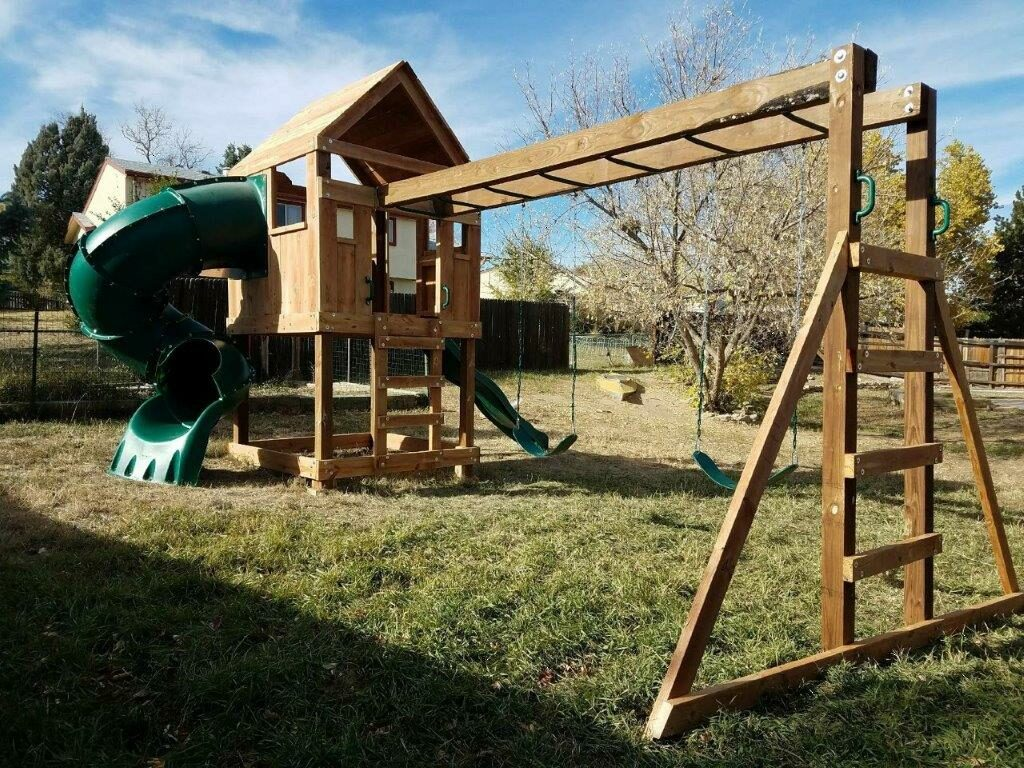 5'x5' Clubhouse with wooden roof, 4' Deck height, Standard slide, 5' Enclosed spiral slide, Fireman pole, 12' Monkey bars with dual ladders & 2 Standard swings