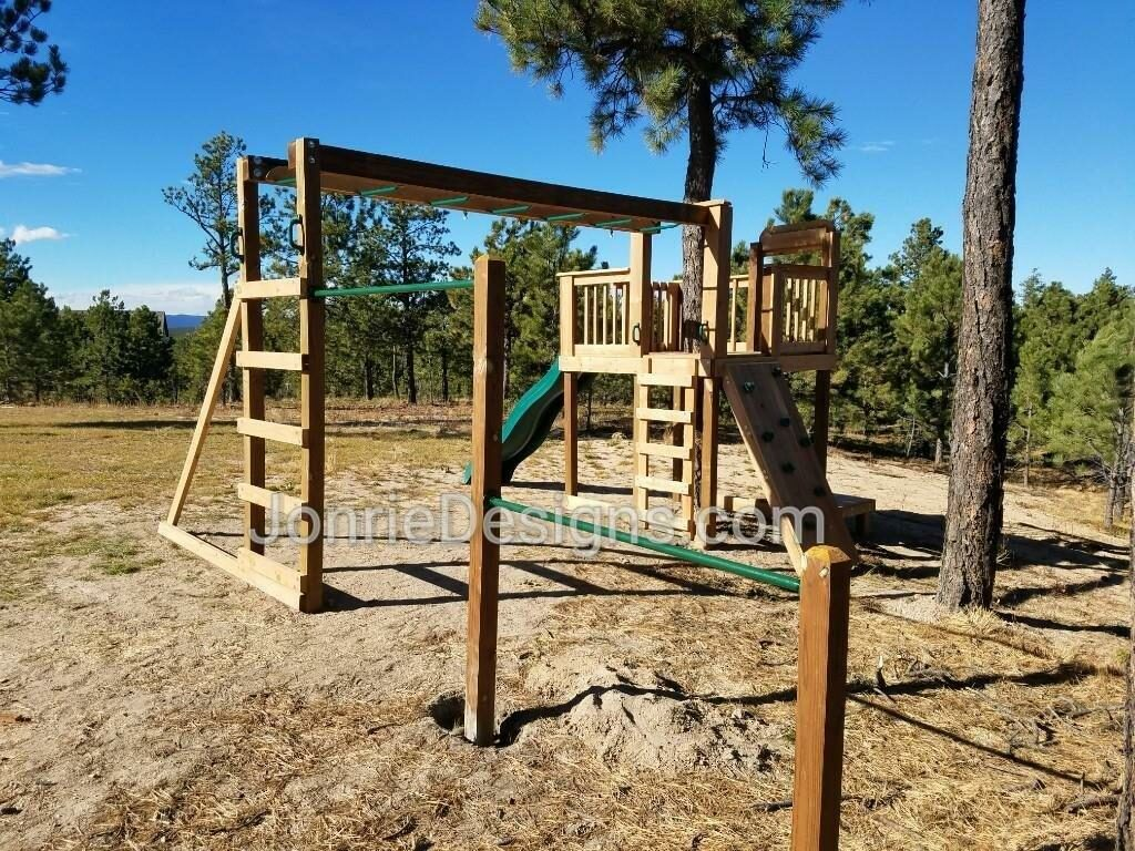 6'x6' Clubhouse with baluster rails around tree, 5' Deck height, Standard slide, Rock wall entry, fireman pole with landing, 8' Monkey bars with dual ladders & gymnast bars