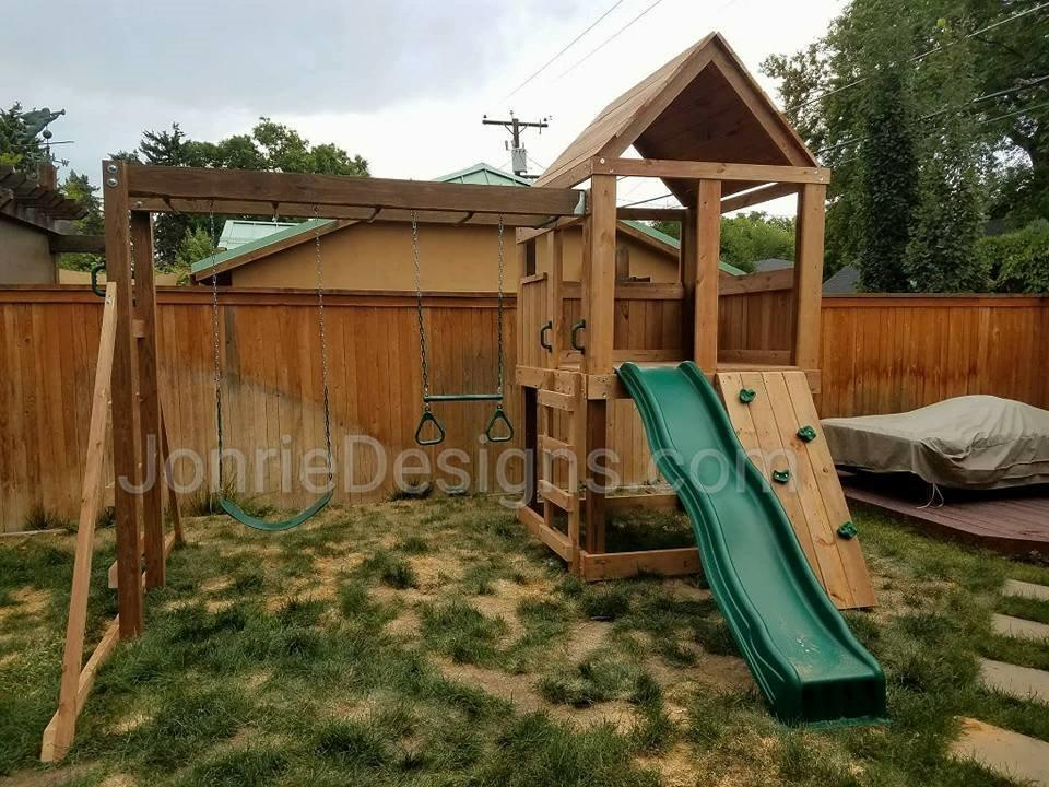 5'x5' Clubhouse with wooden roof, 4' Deck height, Standard slide, Rock wall entry, 8' Monkey bars with dual ladders, Standard swing & Trapeze bar