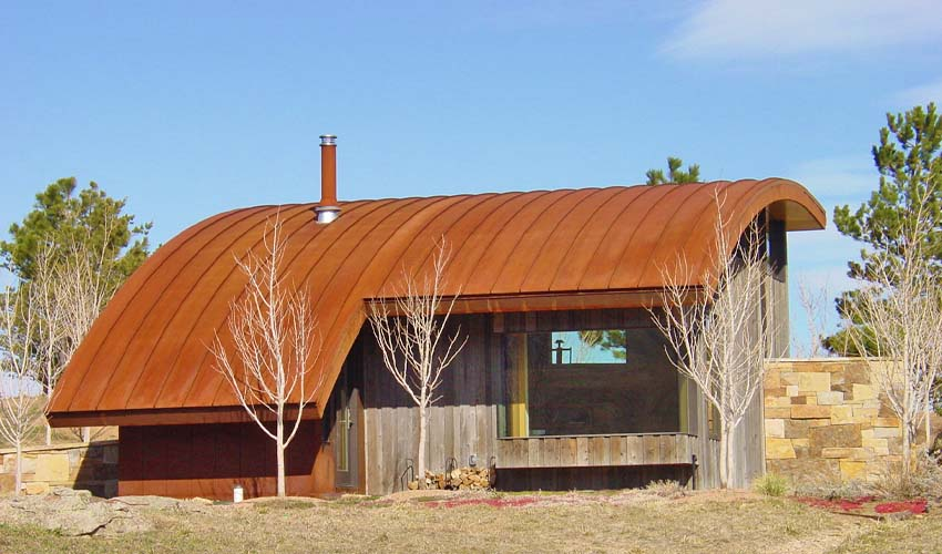 A house with an aged metal roof and reclaimed wood siding.