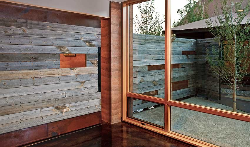 Using grey, reclaimed wood as an element of continuity between the outside and inside of a home or business.