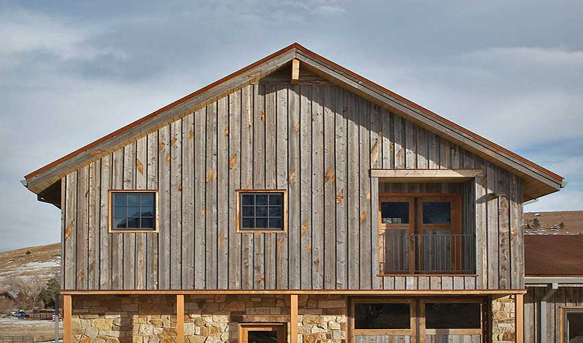 Grey reclaimed wood siding brings about a contrast of color and texture in home design.