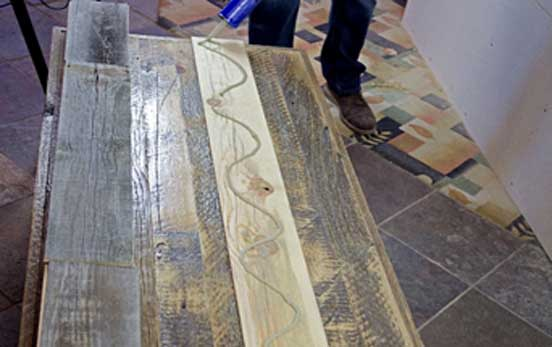 Use an adhesive on the back side of the reclaimed wood planks.