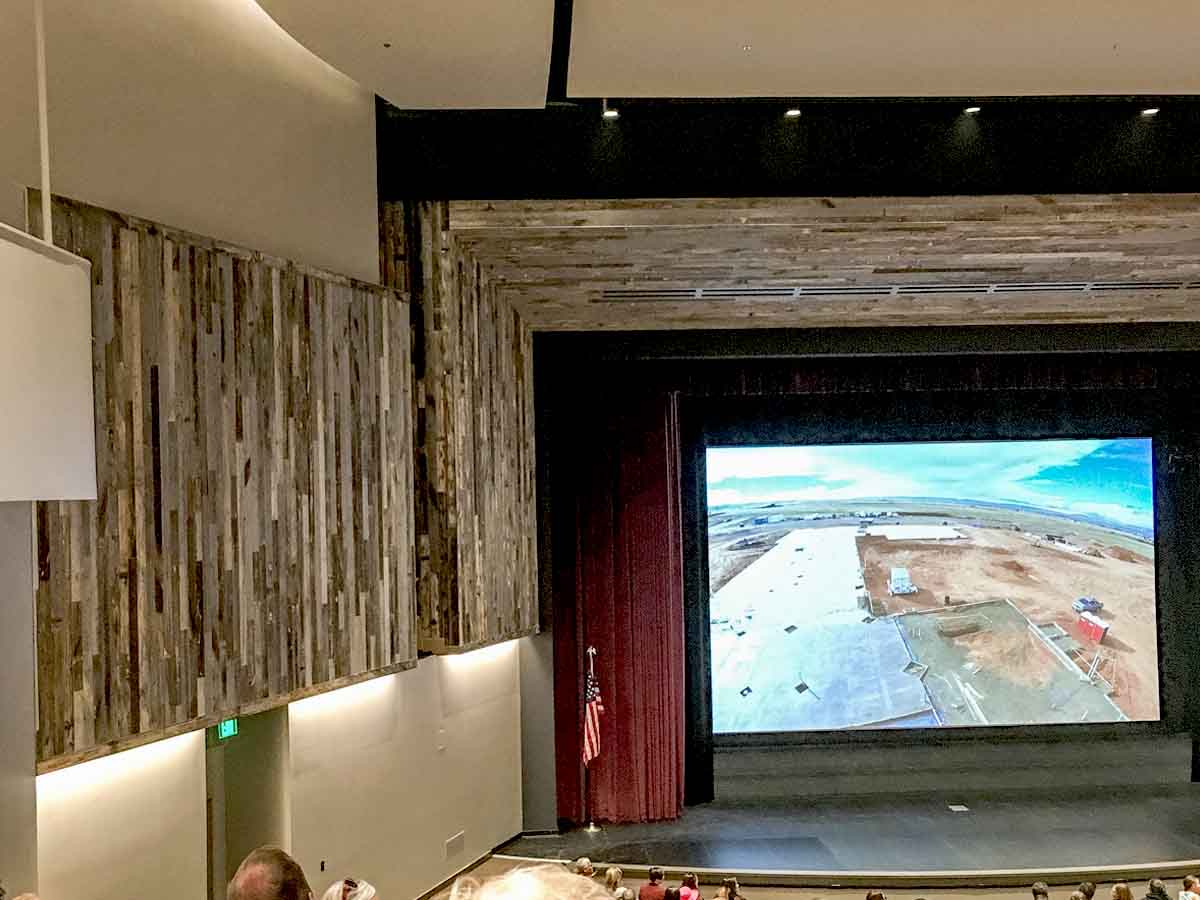 Vertical reclaimed wood wall designs in a high school auditorium.
