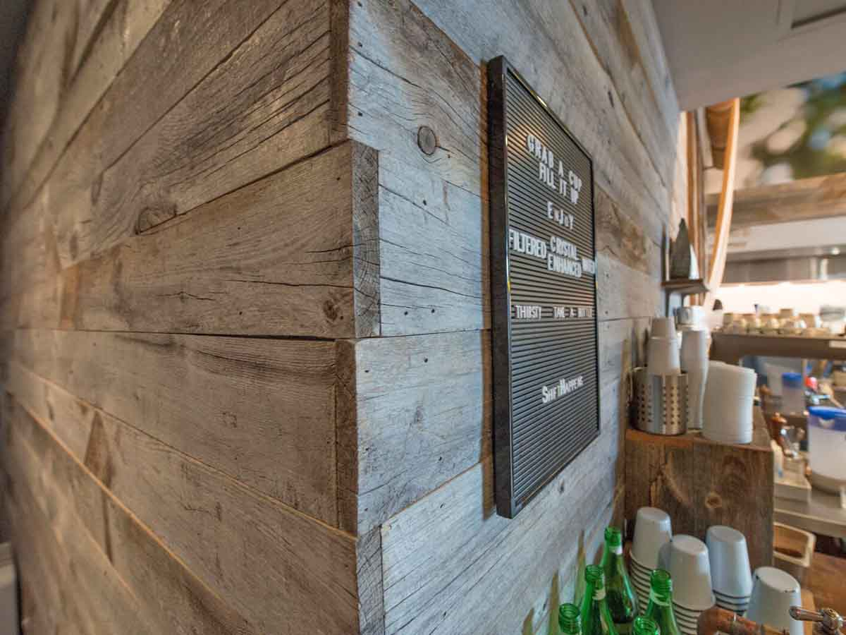 Gray reclaimed wood wall designs with natural edges in a restaurant.