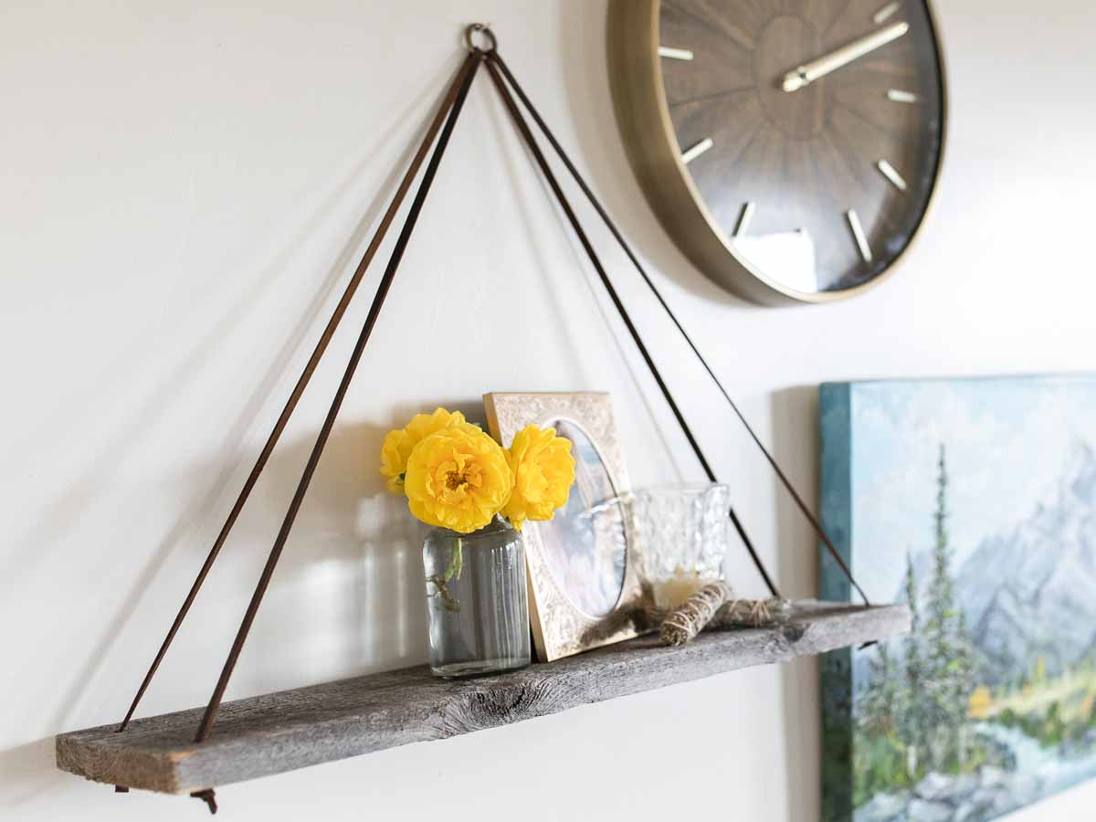 Reclaimed wood wall decor thin ringed leather strap shelf.