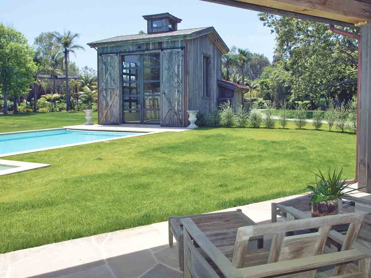 Vertical reclaimed wood siding on pool house in Malibu, Ca using recycled Wyoming snow fence planks.