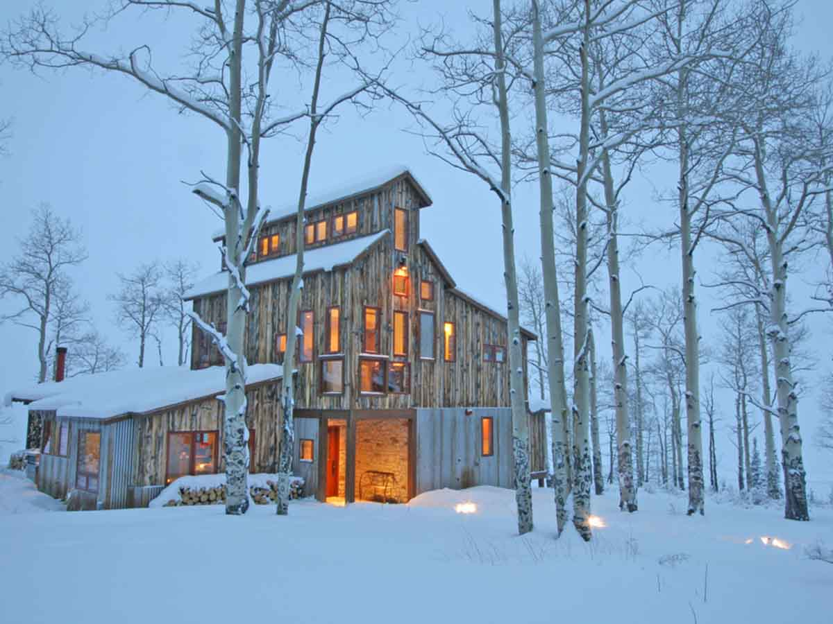 Reclaimed wood siding on a Colorado house in Winter inspired by mining architecture.